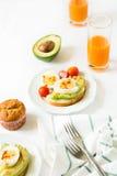Здоровый завтрак: здравицы с кусками авокадоа, томатом, паприкой и яичками Стоковое фото RF