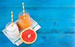 Здоровый завтрак, домодельный югурт, сок и половина грейпфрута на голубой деревянной предпосылке Стоковое Фото