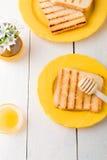 Здоровый завтрак с провозглашанными тост хлебом и медом около вазы с цветками на белой предпосылке Желтый тон Взгляд сверху Стоковые Изображения