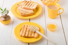 Здоровый завтрак с провозглашанными тост хлебом и медом около вазы с цветками на белой предпосылке Желтый тон Стоковые Фото