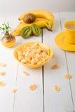 Здоровый завтрак с хлопьями хлопьев и плодоовощ около вазы с цветками на белой предпосылке Желтый тон Стоковая Фотография RF