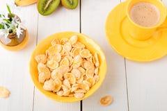 Здоровый завтрак с хлопьями хлопьев и плодоовощ около вазы с цветками на белой предпосылке Желтый тон Взгляд сверху Стоковое Изображение RF