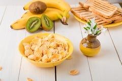 Здоровый завтрак с хлопьями хлопьев и плодоовощ около вазы с цветками на белой предпосылке Желтый тон Стоковые Фото