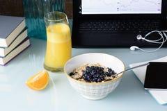 Здоровый завтрак, muesli с ягодами и апельсиновым соком, компьтер-книжка, телефон и книги Стоковые Изображения RF