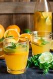 Здоровый лимонад цитруса от известки свежей мяты апельсинов в стеклах и бутылке на темном каменном кухонном столе Стоковое Изображение RF