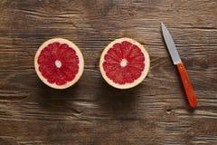 Здоровый органический грейпфрут отрезанный с оранжевым ножом Стоковая Фотография RF