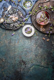 Здоровый травяной чай с листьями и цветками трав на темной деревенской предпосылке Чай с винтажными инструментами и чашкой чаю, в Стоковые Фото