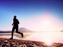 Здоровый уклад жизни Высокорослый бегун молодого человека бежит на взморье восхода солнца Человек скачет в песок Стоковое Фото