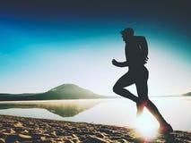 Здоровый уклад жизни Высокорослый бегун молодого человека бежит на взморье восхода солнца Человек скачет в песок Стоковое Изображение RF
