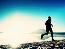 Здоровый уклад жизни Высокорослый бегун молодого человека бежит на взморье восхода солнца Человек скачет в песок Стоковое Изображение