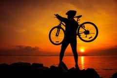 Здоровый уклад жизни Силуэт велосипедиста нося его велосипед Стоковое фото RF