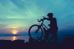 Здоровый уклад жизни Силуэт велосипедиста стоя с велосипедом на Стоковое Изображение
