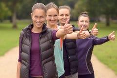 4 здоровых женщины в линии показывая большие пальцы руки вверх Стоковые Изображения