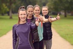 4 здоровых женщины в линии показывая большие пальцы руки вверх Стоковое фото RF
