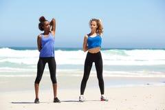 2 здоровых молодой женщины протягивая тренировку на пляже Стоковые Изображения RF