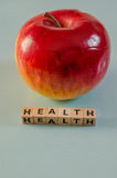 Здоровье слова написанное в кубах и яблоке Стоковые Изображения RF