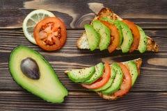 Здравицы с авокадоом и томатом на деревянном столе Стоковые Фото