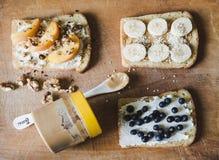 Здравицы с арахисовым маслом, сыром и плодоовощами на деревянной предпосылке Стоковая Фотография RF