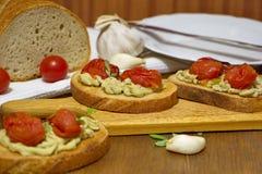 Здравицы с испеченными томатами, домодельной сливк брокколи и чесноком Стоковые Фото