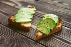 Здравицы с перцем и солью авокадоа на деревянной таблице Стоковые Изображения