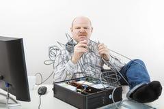 Злющим кабели бизнесмена запутанные удерживанием компьютера на столе Стоковая Фотография