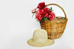 Зink peonies? hat in a wicker basket stock photos