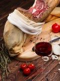 Иберийское negra pata ветчины от Испании, томатов, колец лука и красного бокала Специи на таблице Стоковые Фотографии RF