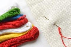 Игла в холсте с потоками других цветов для вышивки Конец макроса вышивки вверх Стоковое Изображение
