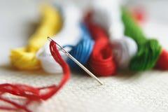 Игла в холсте с потоками других цветов для вышивки Конец макроса вышивки вверх Стоковые Изображения