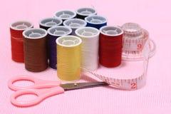 Игла, scissor, продевает нитку, метр портноя, на розовой предпосылке стоковые фотографии rf