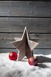 Играйте главные роли сферы рождества украшения красные на куче снега против деревянной стены Стоковое Изображение RF