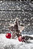 Играйте главные роли сферы рождества украшения красные на куче снега против деревянной стены Стоковая Фотография
