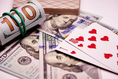 Игральные карты на стоимости банкнот 100 долларов США на белой предпосылке стоковые изображения rf