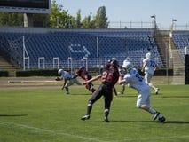 Играть американский футбол на стадионе Стоковые Фотографии RF
