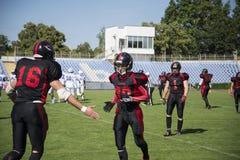 Играть американский футбол на стадионе Стоковое Фото
