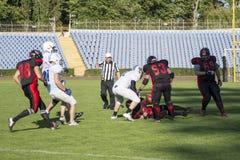 Играть американский футбол на стадионе Стоковые Фото