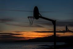 Играть баскетбол в заходе солнца стоковые фотографии rf