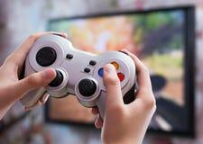Играть видеоигру с регулятором в руках стоковые фото