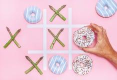Играть в игре пальца ноги tak tik с donuts и спаржей Здоровье nu Стоковые Изображения RF