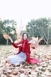 Играть девушки предназначенный для подростков с листьями осени вверх в воздухе в парке осени стоковые фото