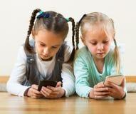 Играть девушек онлайн с телефонами Стоковые Изображения RF