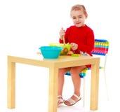 Играть девушки, сидя на таблице Стоковые Фотографии RF