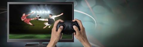 Играть компютерную игру футбола с регулятором в руках Стоковое Изображение