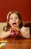 Играть маленькой девочки крытый с глиной Стоковые Изображения