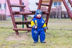 Играть мальчика внешний на спортивной площадке города Стоковые Фотографии RF