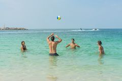 Играть молодые люди волейбола с шариком в воде на b Стоковое Фото