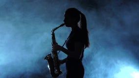 Играть музыканта силуэта женский на саксофоне Закоптелая студия, замедленное движение сток-видео