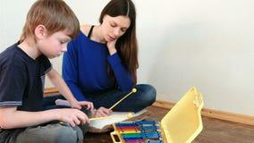 играть нот аппаратуры Повторения мальчика для учителя играя примечания на ксилофоне сток-видео