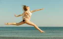 Играть платья женщины нося, скача около моря Стоковое фото RF