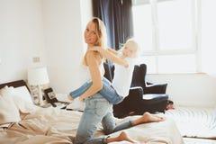 играть семьи счастливый домашний Дочь матери и малыша ослабляя и имея потеху в кровати Стоковое Изображение RF